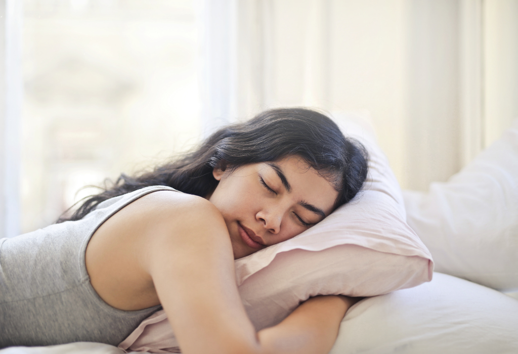 Woman sleeping cuddled up with a pillow