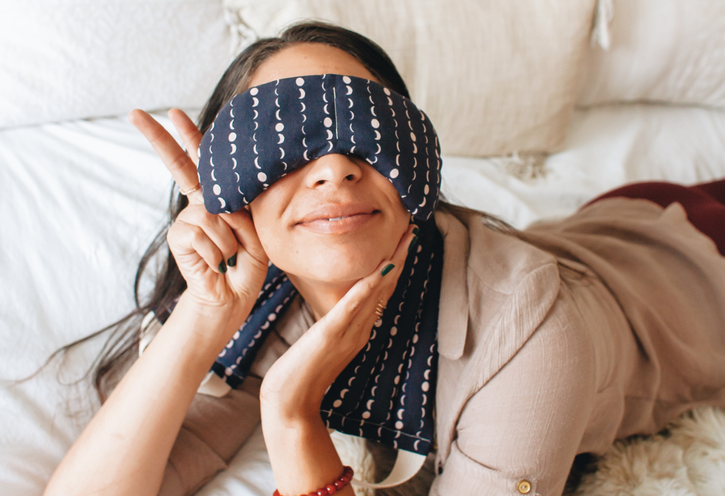 Woman laying on her belly with eye mask on and posing with a peace sign