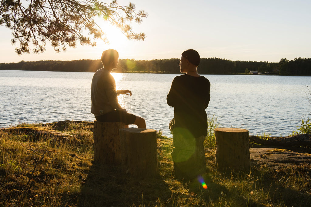 two people talking one on one by a lake