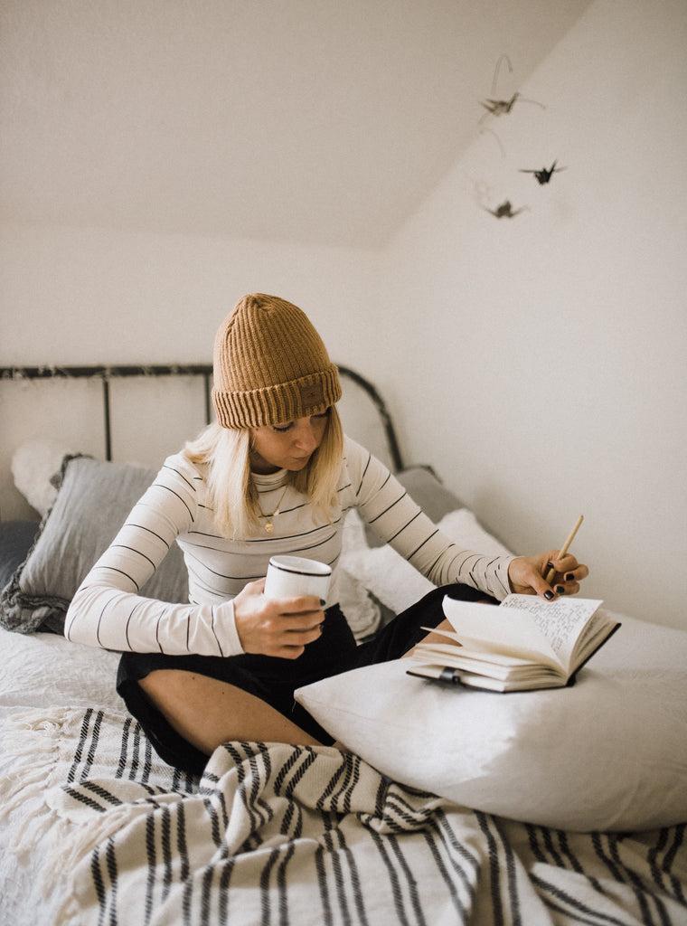 woman gratitude journaling in the morning with coffee