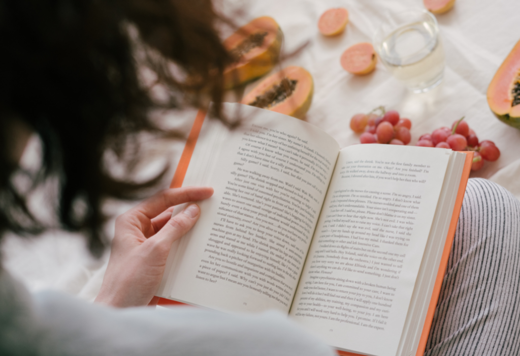 woman reading a book with fruit around her in bed