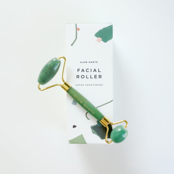 Green adventurine crystal facial roller with gold lining on a white box