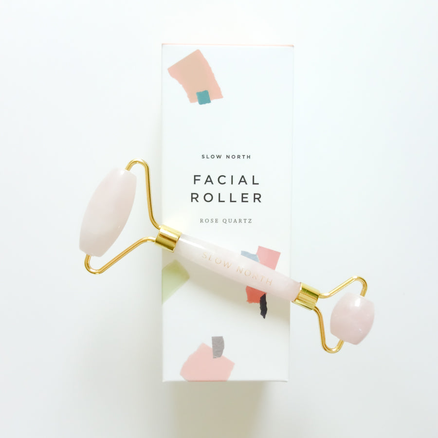 Rose quartz crystal facial roller with gold lining on a white box