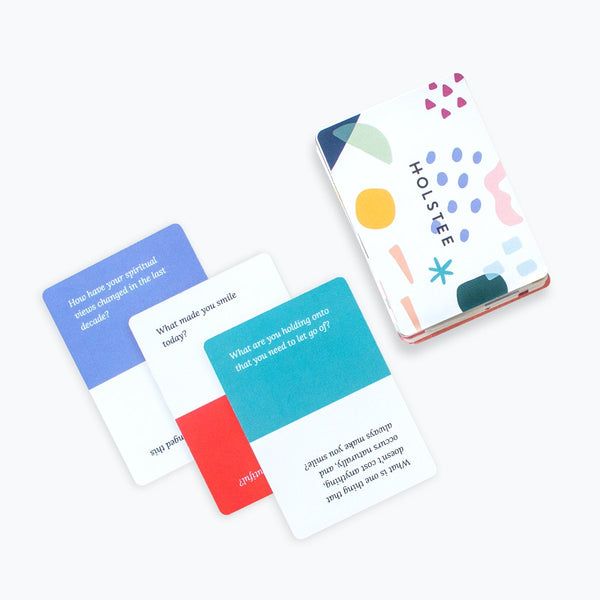 three cards next to deck of Holstee cards on a white background