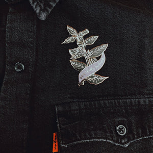 Large pin with magically inclined banner on jean jacket