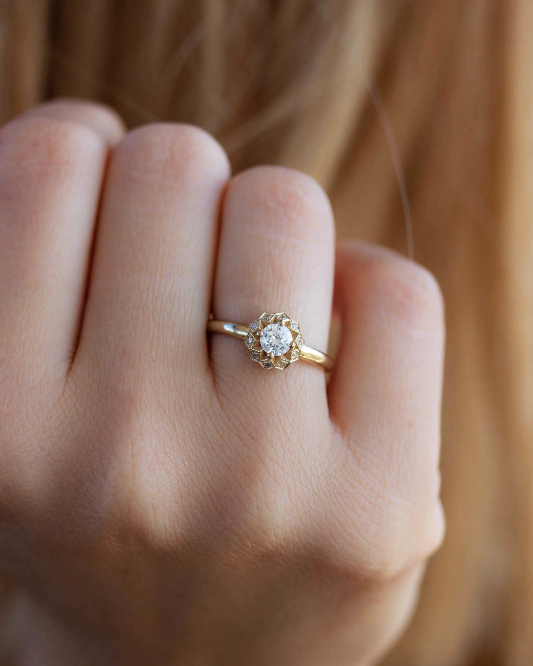 A delicate 14k yellow gold engagement ring, set with a center brilliant cut white diamond and smaller diamonds around it, in the shape of a geometric flower.