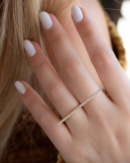 A dainty 14k yellow gold two finger ring, with a long bar set with white diamonds, that covers both fingers.