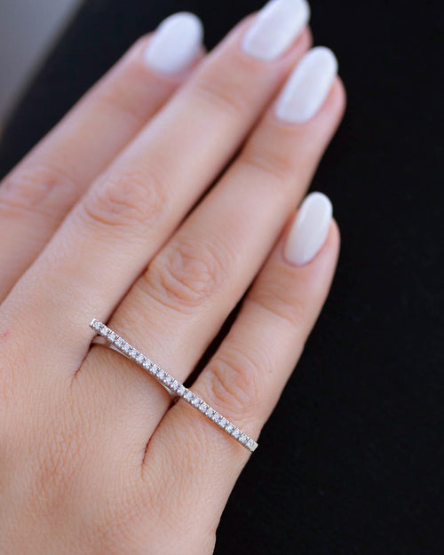 A dainty 14k white gold two finger ring, with a long bar set with white diamonds, that covers both fingers.