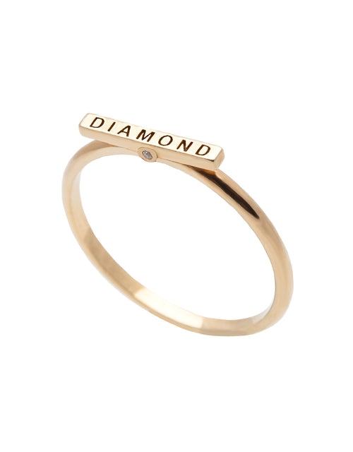 A delicate 14k yellow gold ring, engraved with DIAMOND on top and set with two tiny white diamonds.