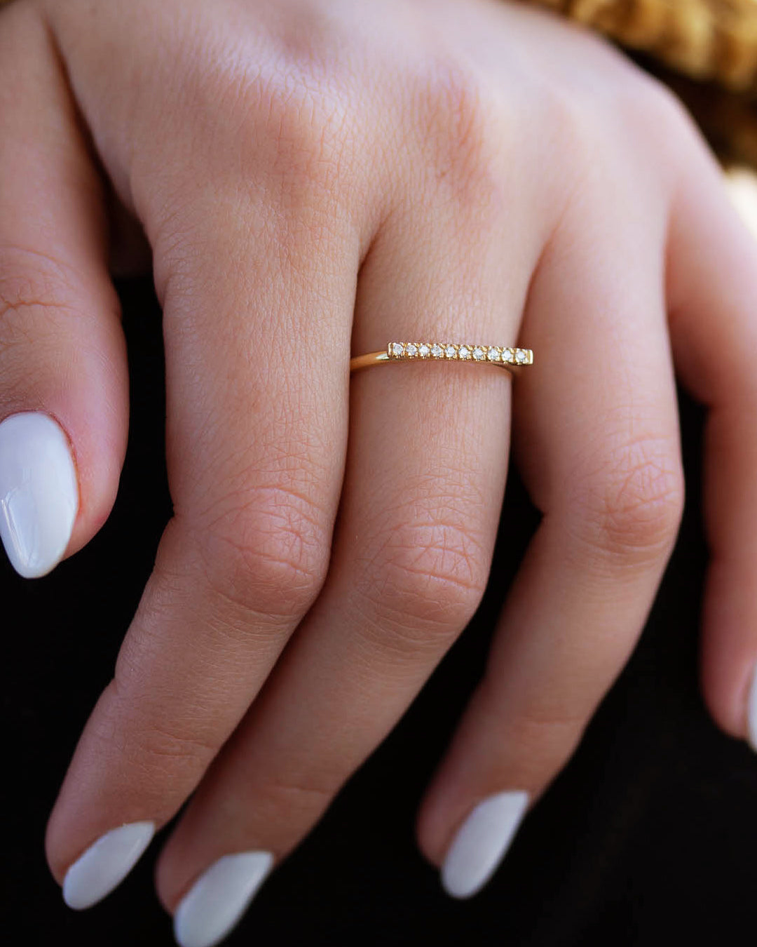 A dainty 14k yellow gold ring, with a horizontal bar on top, set with nine tiny white diamonds.