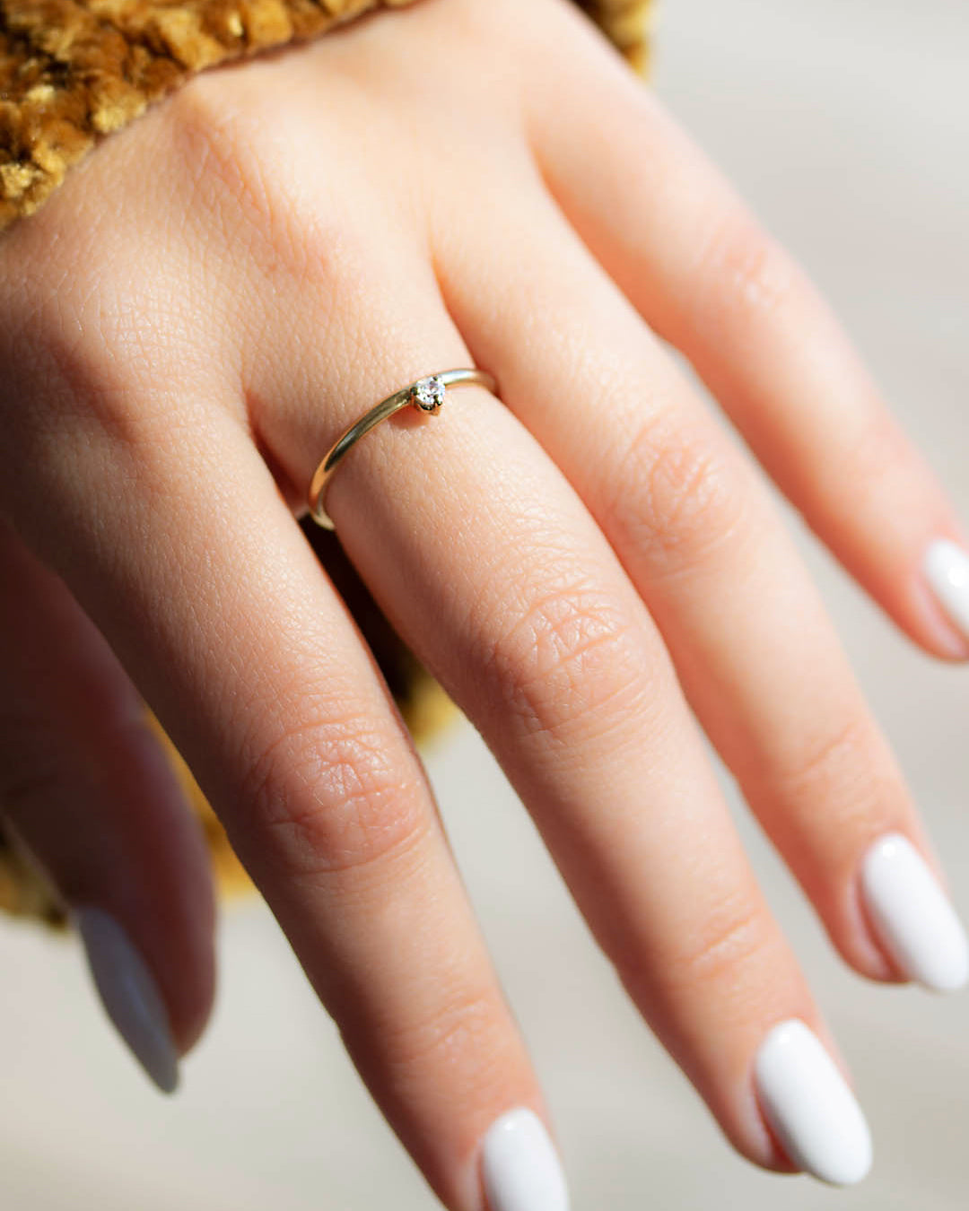 A dainty 14k yellow gold ring, set with one tiny, brilliant cut white diamond.
