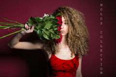 Brand image of young black woman wearing Lava Pool Crop Top holding bouquet of roses against the face.