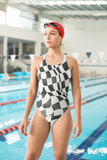 Photo of female model standing by a pool lap wearing B&W Checker Sway Swimsuit (full price $45.00)