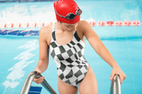 Photo of female model stepping out of pool wearing B&W Checker Sway Swimsuit (full price $45.00)