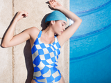Photo of female model laying on poolside floor wearing Blue Checker Sway One-piece Swimsuit (full price $45.00 USD).