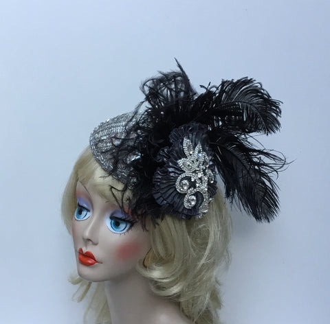 """SYLVIA""  is a metallic silver fabric with rhinestone appliqué,          and ostrich feathers."