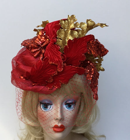 """Merry"" a red Christmas hat embellished with a red Poinsettia and net."