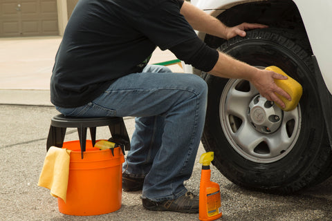 Man sitting on The Original Bucket Stool™ washing automobile tire with detailing products