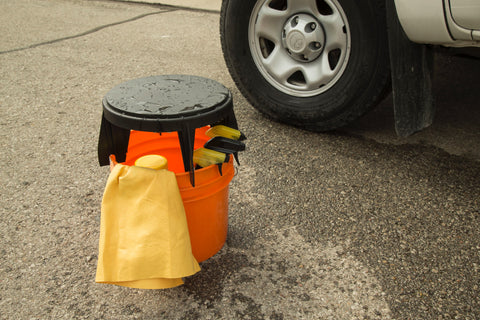 The Original Bucket Stool™ shown by itself on top of a bucket with car detailing supplies on street by pickup tire. Water on top of Bucket Stool™ shows that it's waterproof.