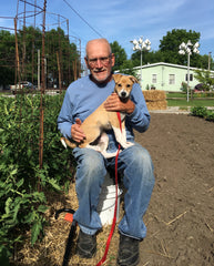 Roger Kammeyer, pictured with his new friend and rescue dog Ringo, in the garden at RWK Solutions, LLC headquarters in Concordia, Missouri.  Purple Martin birdhouses in the background.