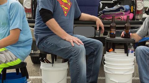 Three people pictured using The Original Bucket Stool™ for tailgating at a sporting event. Click to see tailgating solutions page.