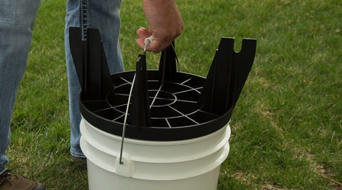 Person carrying bucket by the handle and using The Original Bucket Stool™ upside down as a lid. Click to see convenience solutions page.