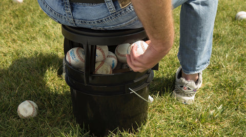 Baseball player sitting on The Original Bucket Stool™ on top of a bucket full of baseballs. Man reaching underneath to grab another ball for more efficient practice. Click to see baseball and softball solutions page.