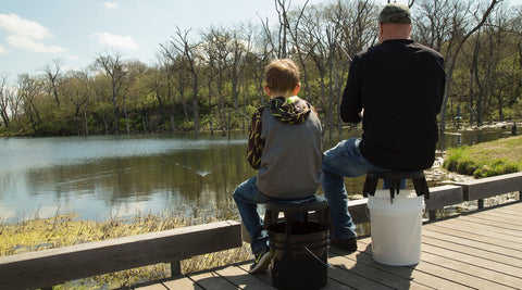 Father and son each using The Original Bucket Stool™ for fishing. Click to see outdoor solutions page.
