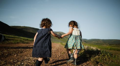 Two little girls climbing a hill holding hands one helping the other
