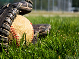 baseball glove on grass with ball in it