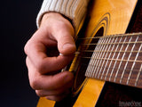 closeup of fingers strumming a guitar