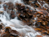 water in creek flows over the orange brown rocks