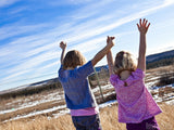 two young girls lifting joined hands high