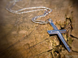 silver cross pendant on wood background