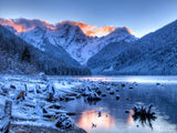 snow covered shore of lake winter mountains background