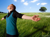 woman in field worships with arms out