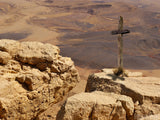 wooden cross on desert rock