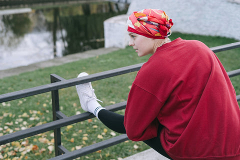 Woman in Red Sweater and White Pants Sitting on Black Metal Railings