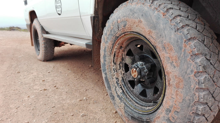 In the foreground and in sharp focus is NutWare's Black loose wheel nut indicators on a black steel rim. The tyre, rim and mudguards are sprayed with a sandy brown granular mud. The ground level angled shot shows the running step, lower body and back tyre of a white 76 Series Toyota Landcruiser. The blurred background shows coastal shrubbery  in shades of green with the ocean horizon far off in the distance.
