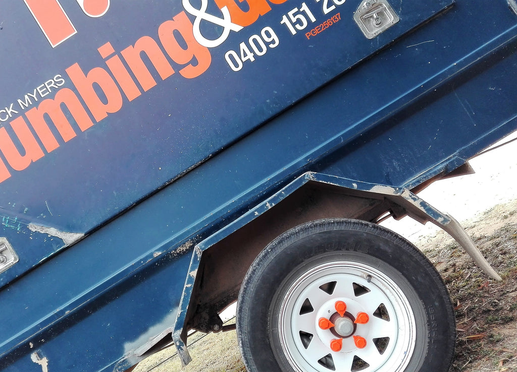 A tradie's trailer, workman's trailer, fitted with NutWare Orange Extended Wheel Nut Indicators, which are able to indicate excessive heat and loosening or lost wheel nuts. Australian Made.