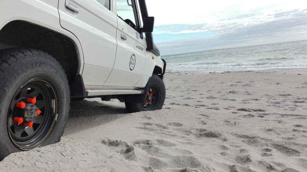 Four wheel driving on the beach in South Australia with NutWare's Land cruiser, fitted with oragne Loose Wheel Nut Indicators. Protecting the wheel nut from sand and damage, and able to indicate excessive heat the wheel nut loosening and loss. Australian made, available from NutWare.