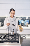 Woman scooping Prana Chai out of packet