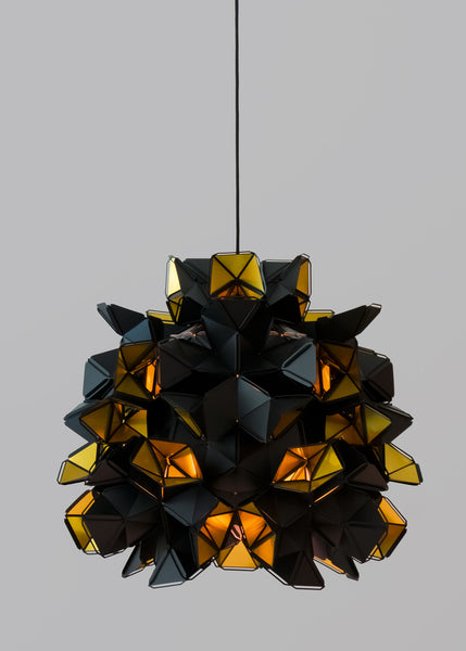 The Labyrinth Lamp is a light sculpture by Republiken.  Featured in this image with an open bottom to let light flood out. The outside of the Labyrinth light sculpture has a matte black surface which contrast the protruding openings where the reflective inside is exposed.
