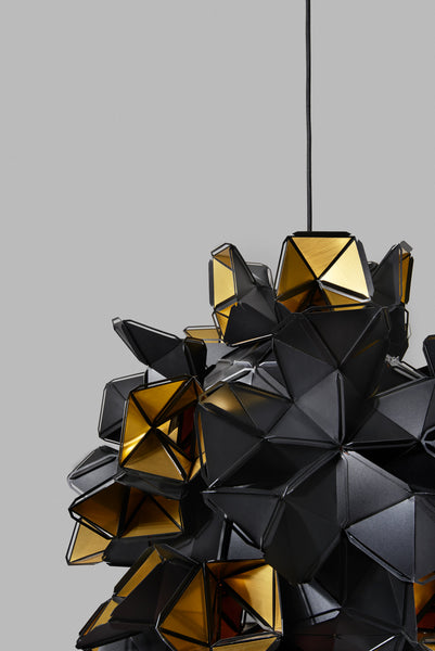 The Labyrinth Lamp is a light sculpture by Republiken. Hang it like a chandelier! The outside of the Labyrinth light sculpture has a matte black surface which contrast the protruding openings where the reflective inside is exposed.