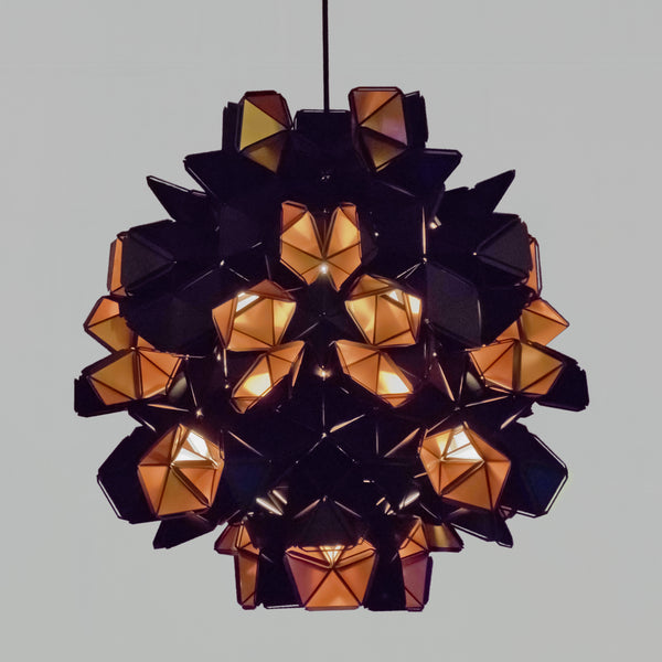 The Labyrinth Lamp is a light sculpture by Republiken. Hang it like a chandelier! The outside of the Labyrinth light sculpture has a matte black surface which contrast the protruding openings where the reflective inside is exposed