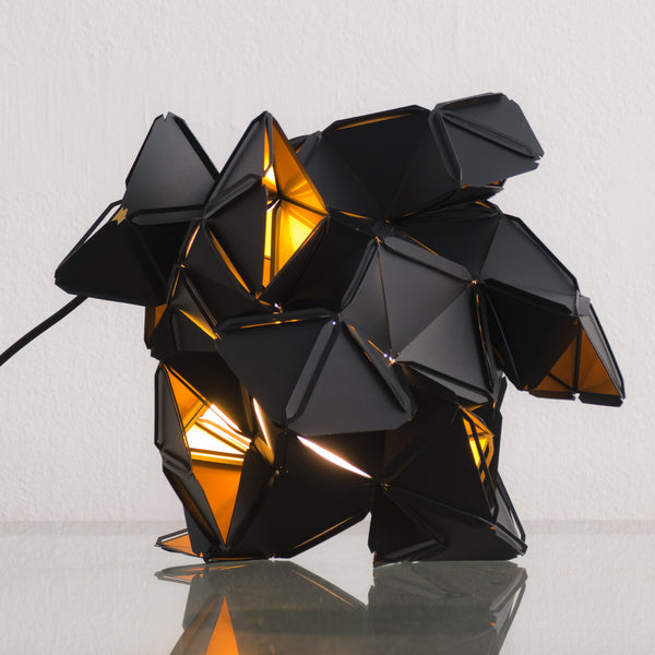 The little Labyrinth lamp is a light sculpture by Republiken. Designed by Jakob Uhlin. Use it as a pendant or as a table light. the golden reflective inside is in strong contrast to the matte black outside.