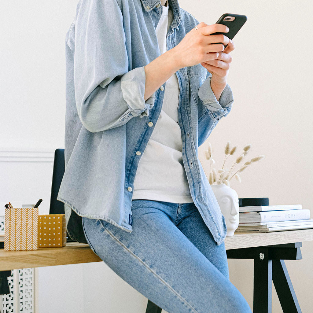 Leaning against desk checking phone