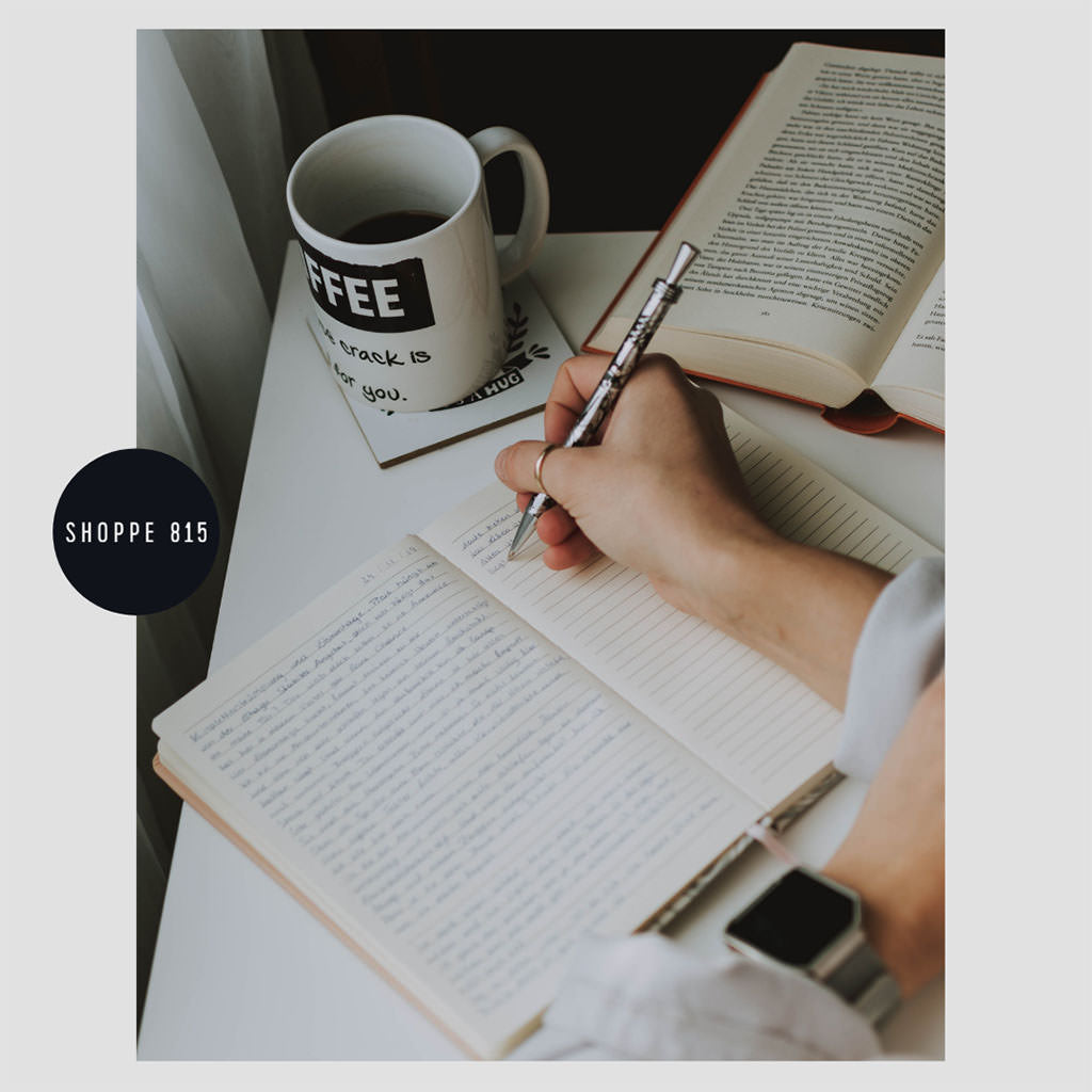 Writing in notebook with coffee