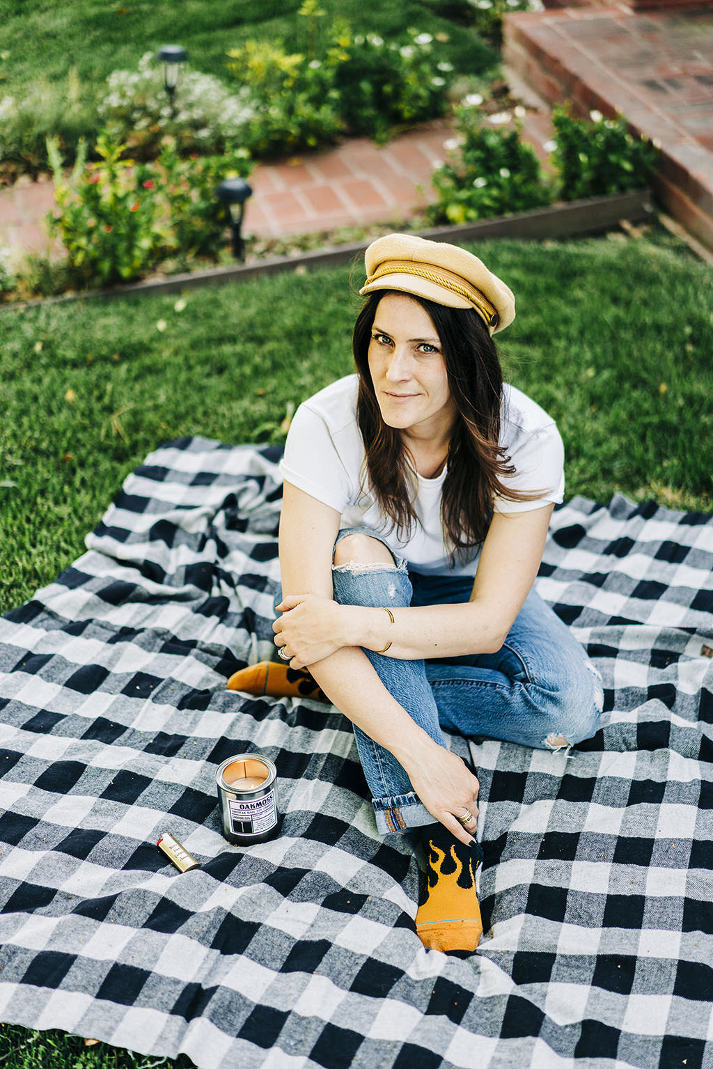 Katy the founder of Shoppe 815 sitting on a picnic wearing flame socks with a tin candle lit.