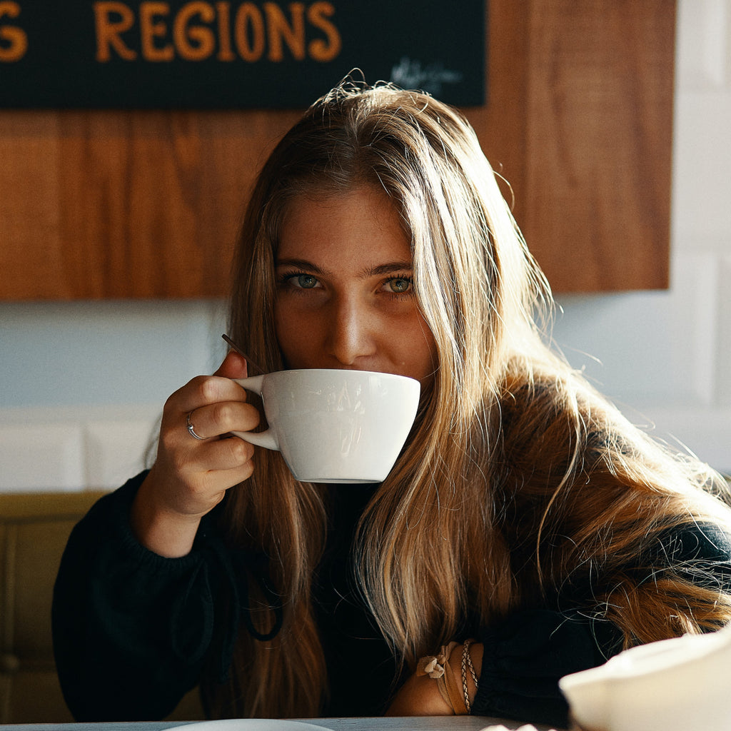 A woman enjoying her morning coffee in a white mug while relaxing.